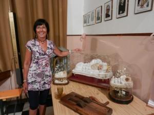 Aurora Cantini a Poscante di Zogno con la teca in vetro della Maria Bambina e alcuni oggetti di un tempo
