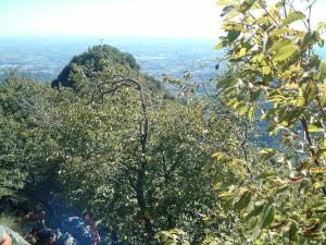 La croce sulla cima sud del Monte Podona tra gli alberi e la pianura bergamasca