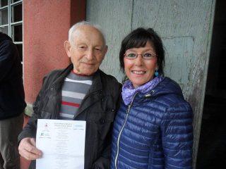 """Avraham Aviel riceve la copia della poesia """"Anniversario Sciesopoli"""" dallla poetessa Aurora Cantini, davanti al portone di Sciesopoli, 17 aprile 2016"""
