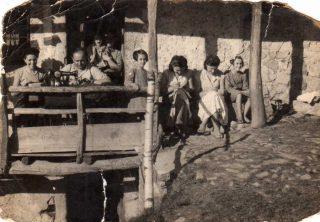 Il misterioso sarto sfollato a Ganda e la sua inseparabile macchina di cucire. Accanto a lui la giovanissima Clemens Noris, mamma di Aurora Cantini, con la mano appoggiata alla staccionata. Le ragazze di Ganda impararono a cucire. Ragazze di cucito, Ganda, 1943.